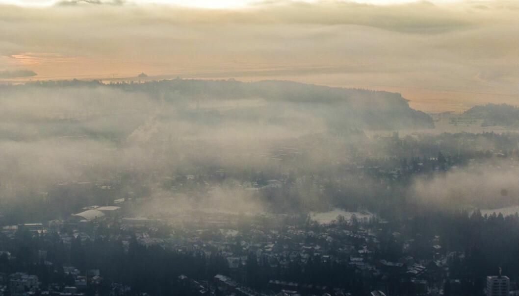 Oversiktsbilde tatt fra Holmenkollbakken fredag formiddag. Kaldt vær og forurensing fører til at luft presses ned i skoddehavet over Oslo.  (Foto: Vegard Grøtt / NTB scanpix)