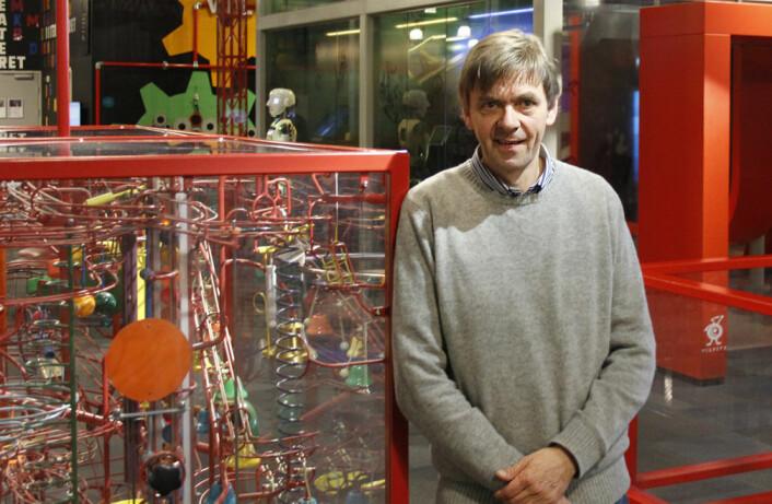 Nils Petter Hauan på VilVite vitensenter i Bergen. Her står han foran Flerkuleriet, et eksperiment med kuler som dras ned av tyngdekraften langs forskjellige baner. (Foto: Petter Soltvedt, VilVite)