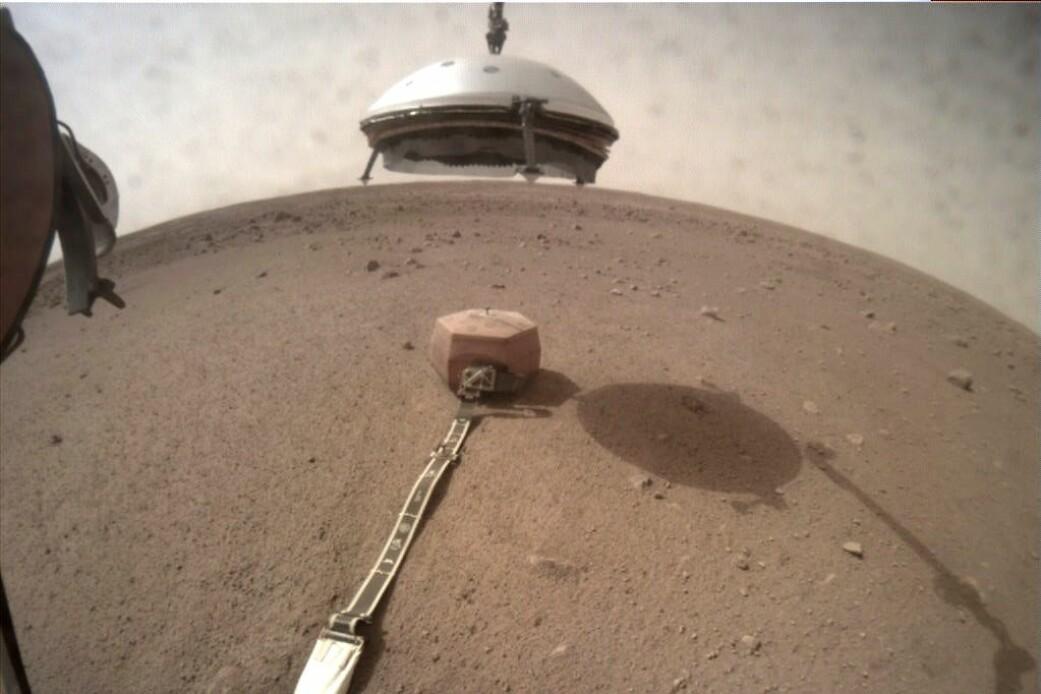 Insights robotarm senker skjoldet ned over seismometeret. (Foto: NASA/JPL-Caltech)