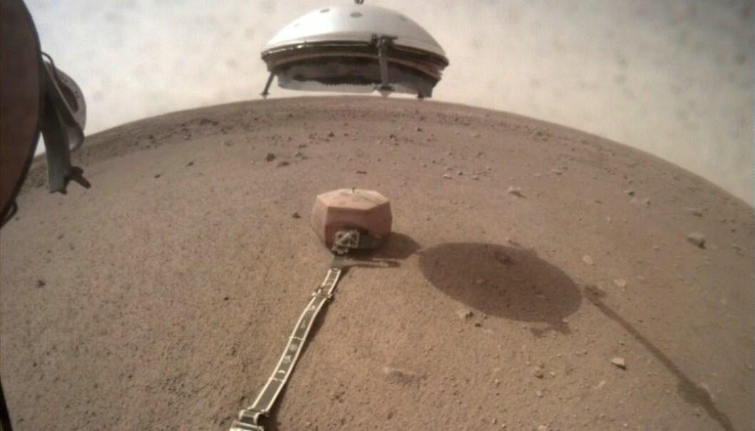Den hvite kuppelen er et skjold. Her senker InSight skjoldet ned over måleapparatet. (Foto: NASA/JPL-Caltech)