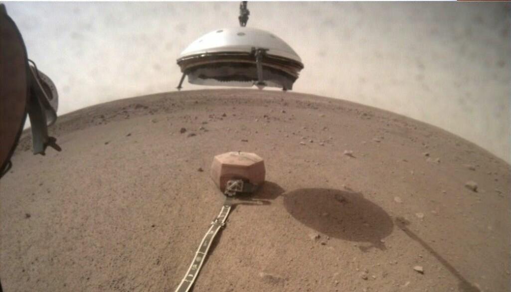 Her er InSight på Mars. Den bruker robot-armen til å heise ned et skjold over jordskjelv-måleren. (Foto: NASA/JPL-Caltech)
