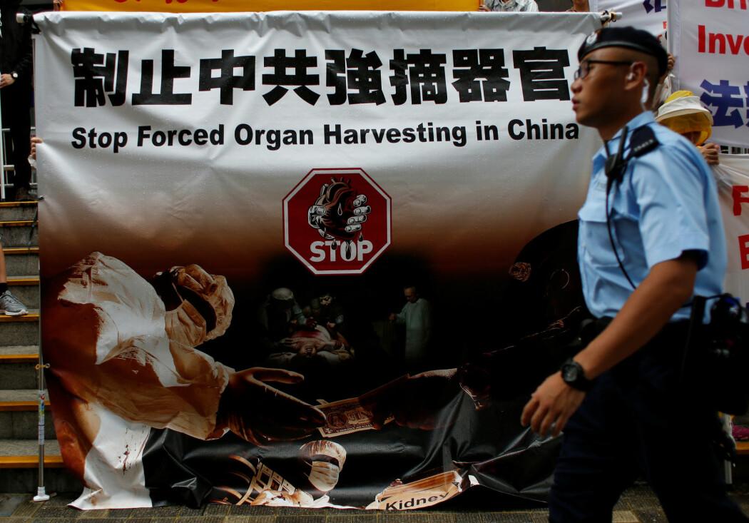 Hong Kong, 2016: En politimann går forbi en plakat som protesterer mot bruk av organer fra henrettede Falun Gong-medlemmer. (Foto: Bobby Yip, Reuters/NTB scanpix)