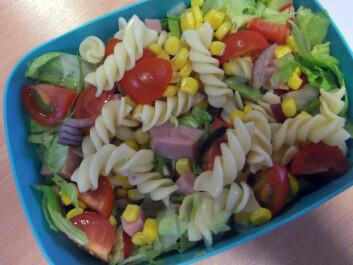 Salat med pastaskruer, tomater, salat, skinke, løk og mais.
