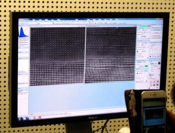 De hvite prikkene er atomkolonner, og man ser forskjell på de ulike atomene ved at tunge atomer gir sterkere kontrast enn de lettere atomene. På bildet til høyre dras en lett kontorstol over gulvet i naborommet til elektronmikroskopet mens bildet tas. Det lille, varierende magnetfeltet fra stolen i naborommet er nok til å gi store forstyrrelser i bildet, og viser hvor sensitivt et av verdens beste elektronmikroskop er med hensyn på at det må lokaliseres i stabile omgivelser. (Foto: Per Henning/NTNU)