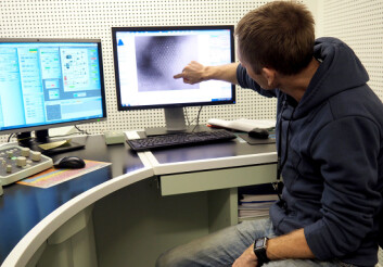 Per Erik Vullum viser et elektronmikroskopi-bilde hvor vi ser enkeltatomene i ett av de små kornene i batteri-elektroden. (Foto: Per Henning/NTNU)
