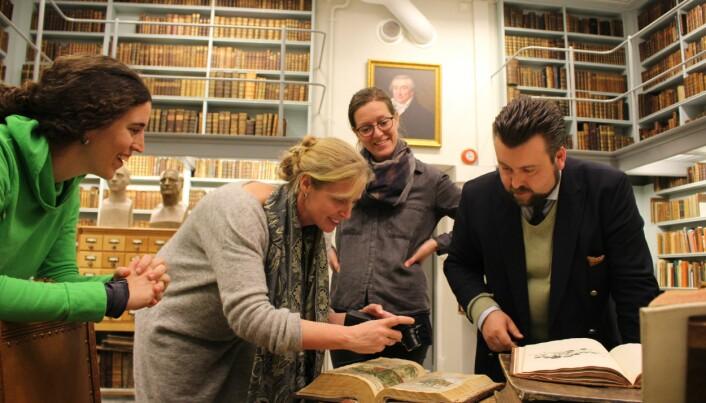 Irene Teixidor-Toneu (t.v.), Anneleen Kool og Karoline Kjesrud gjorde mange morsomme oppdagelser da de ble guidet gjennom historiske plantebøker av Ernst Bjerke, forvalter av Oslo katedralskoles historiske boksamling. (Foto: Dag Inge Danielsen, UiO)