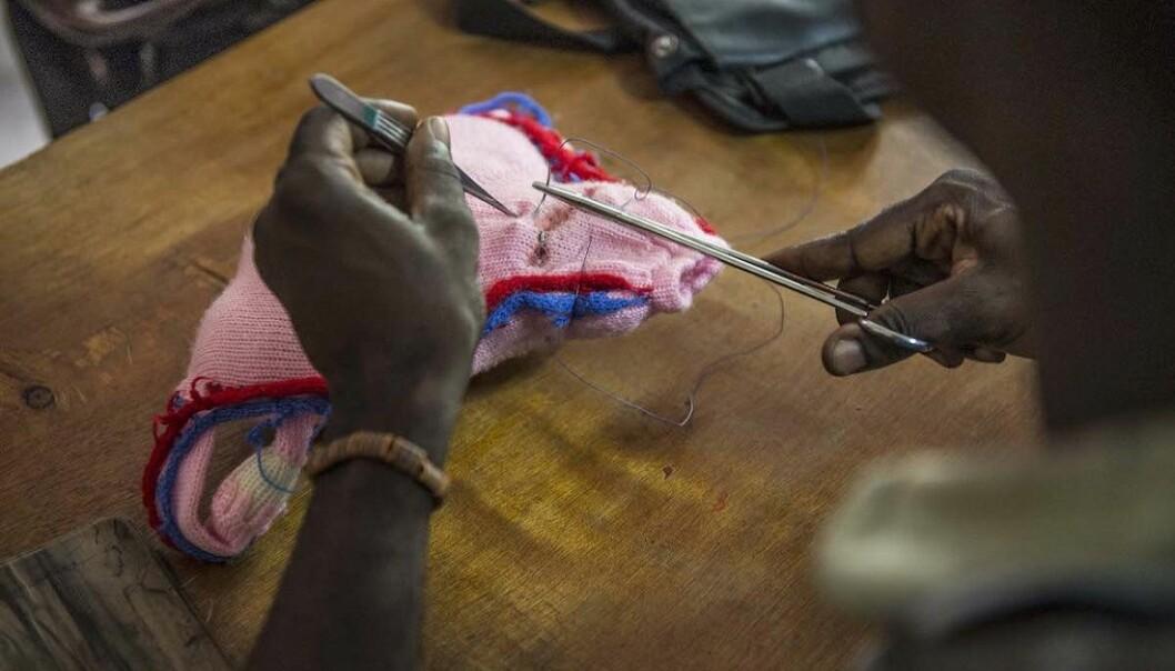 Studentene øver seg i å sy på en strikket versjon av en livmor. En oppfinnsom måte å lære på. (Foto: Magnus Endal, CapaCare)