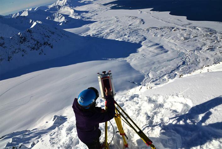 Alexander Prokop, skredforsker ved UNIS, bruker en terrestrisk laserskanner for å måle snødybde på Svalbard. (Foto: Privat)