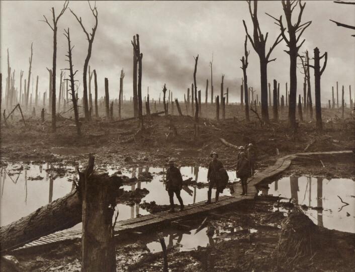 Fem soldater foran det vanvittig ødelagte landskapet i nærheten av Ypres under slaget ved Passchendaele. (Foto: Frank Hurley)