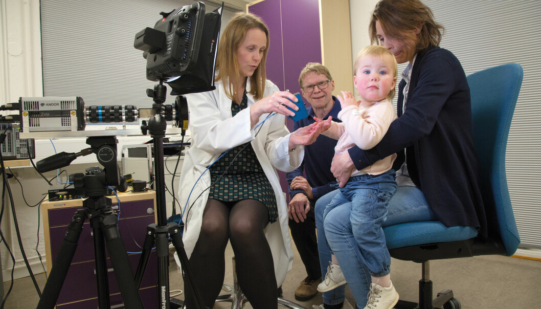 Lise Lyngsnes Randeberg utvikler en ny optisk målemetode som skal gjøre det lettere og raskere å oppdage den plagsomme hudbetennelsen atopisk eksem. Hun tester ut metoden på datteren til Inger Marie Gryting, Victoria Gryting (2 år). Per Lagerløv leter nå etter flere barn til uttestingen.  (Foto: Yngve Vogt)
