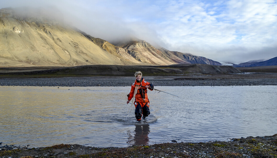 Forskar Pernilla Carlsson ved NIVA går i land frå Ebbaelva ved Petuniabukta, Svalbard, med ein prøvetakar for miljøgifter i handa. (Foto: Sverre Johansen)