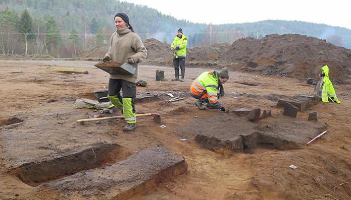 Arkeologer fra Kulturhistorisk museum og Aust-Agder fylkeskommune jobber med å grave frem hellekammeret i grav nummer to. Vevloddene fra den tredje begravelsen hadde forstyrret hellekammeret og lå i det lille søkket til høyre i bildet (Foto: Julian P. Martinsen, KHM)