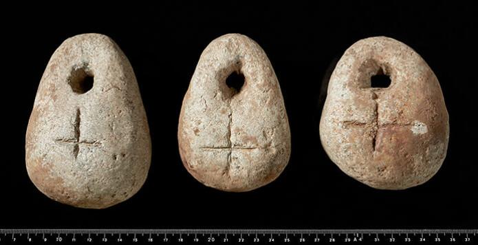 Tre av vevloddene med inngraverte kors, henholdsvis med det som fremstår som et latinsk kors (her opp-ned) og likearmet (Foto: Ellen C. Holte, KHM)