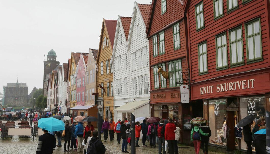Folk har taklet regnet ved Bryggen i Bergen på ulikt vis, både i vår tid og i middelalderen. ( Foto: Erik Johansen / NTB scanpix)