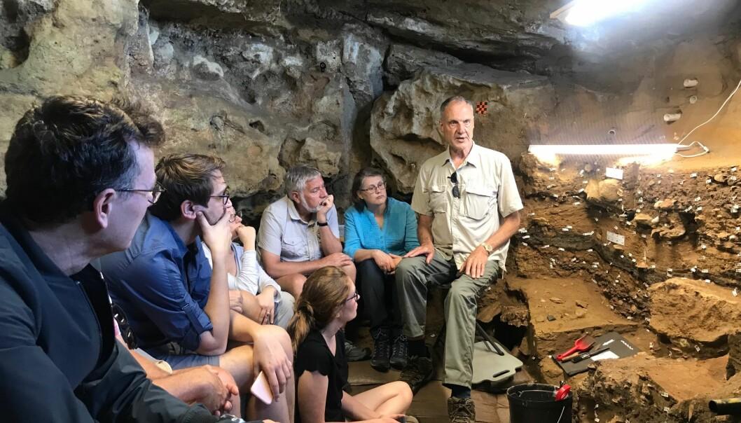 Professor Henshilwood forteller hvordan hulen er bygget opp med ulike kulturlag som stammer fra mennesker som har oppholdt seg i hulen. (Foto: Janne-Beate Buanes Duke / UiB)