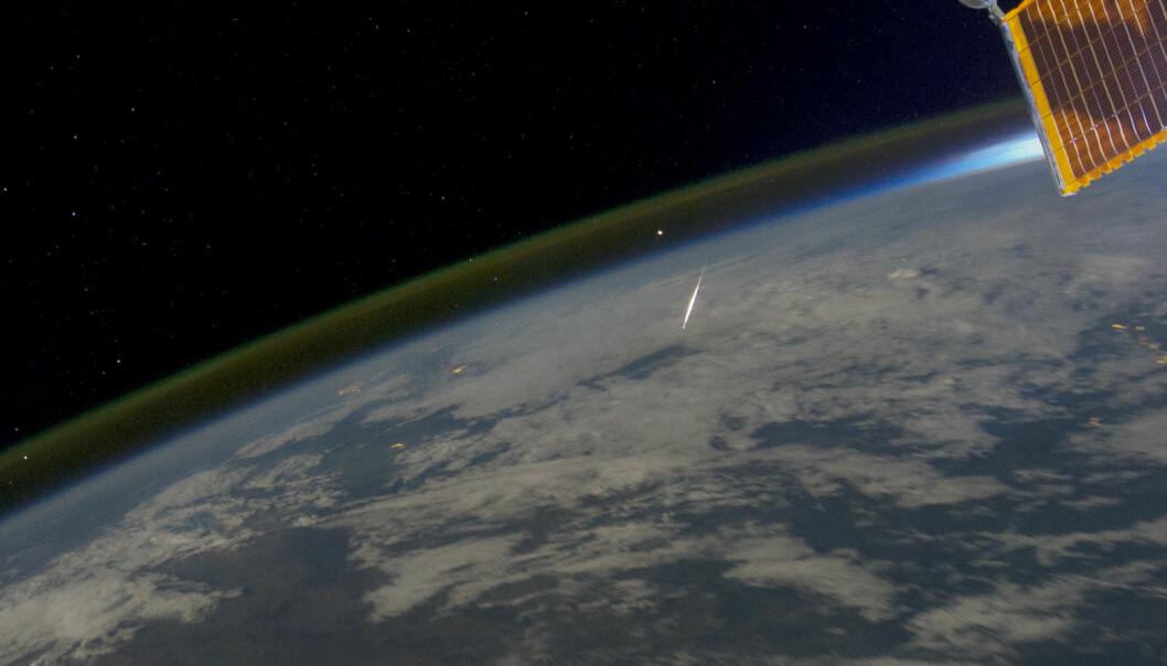Natthimmellys vises som en tynn stripe over jordskorpen og midt i bildet en meteor som brenner opp idet den treffer atmosfæren. Bildet er tatt fra den internasjonale romstasjonen (ISS) over Irkutsk, Sibir, 13. august 2011.  (Foto: NASA Earth Observatory)