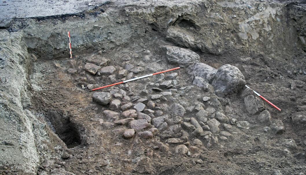 Etter å ha fjerna asfalt og moderne sand og grus, kom eit gamalt vegfar til syne. Analyser av organisk materiale viste at vegen var frå vikingtida.  (Foto: Arkeologisk museum, Universitetet i Stavanger)