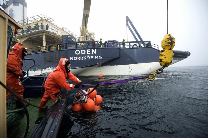 Forskere jobber med å sette ut forankrete sonarer. De skal logge data topografien av isens underside. (Foto: Øyvind Hagen, Statoil)
