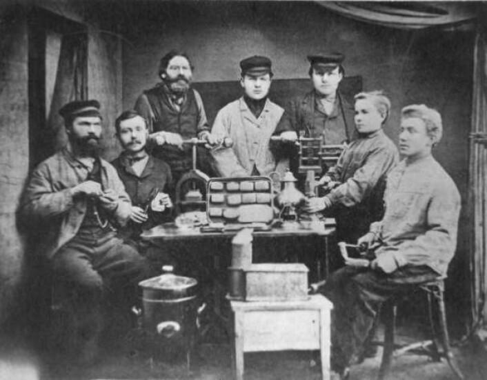 Dette bildet viser Jakob Helvig til venstre og noen av hans ansatte. Hver av personene på bildet illustrerer ett skritt i produksjonen av en håndlaget hermetikkboks. Foto: Norsk Folkemuseum