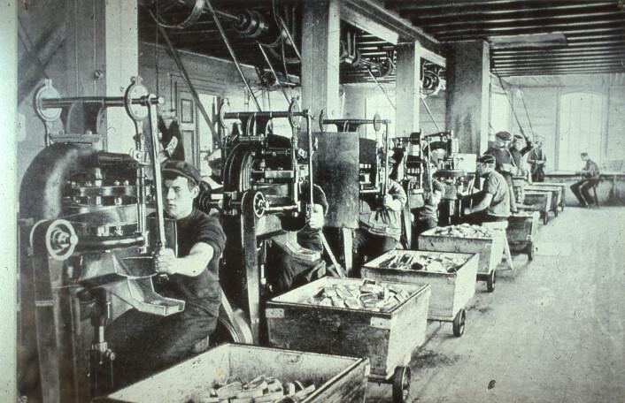 Reinerts falsemaskin i bruk på fabrikk. Denne maskinen kom i 1905 og kunne feste 10 000 lokk på eskene på en 10 timers arbeidsdag. Denne maskinen ble eksportert over hele verden. Foto: MUST/ Norsk hermetikkmuseum