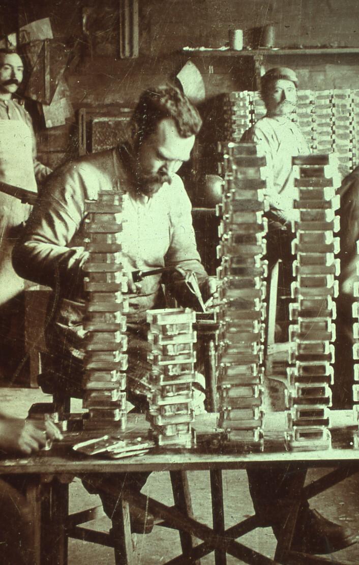 Lodder som fester lokkene på eskene. En god lodder klarte å feste 800 lokk på en time Foto: MUST/ Norsk hermetikkmuseum