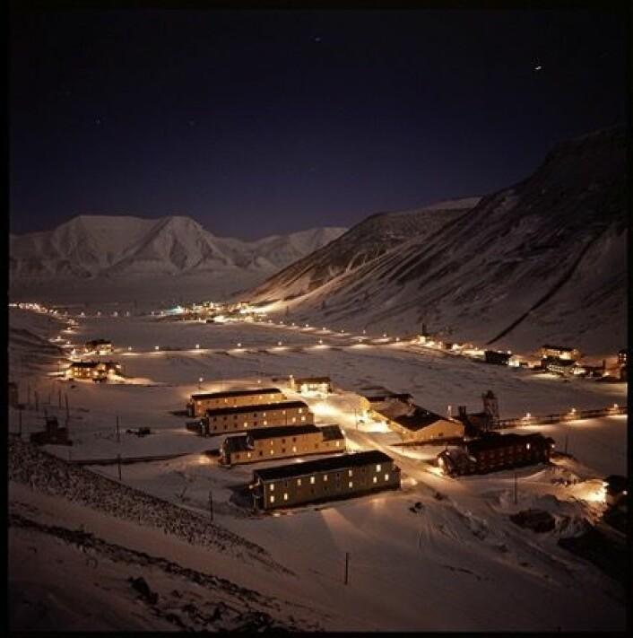 Longyearbyen omkring 1960. Lik andre gruvesamfunn var bosetninga sterkt klassedelt. Nærmest ligger Sverdrupbyen og Nybyen (t.h.) hvor arbeiderne bodde. Ved fjorden og i bakgrunnen ligger boområdet til funksjonærene på Haugen og Skjæringa. (Foto: Herta Lampert. Tromsø Museum – Universitetsmuseet. )