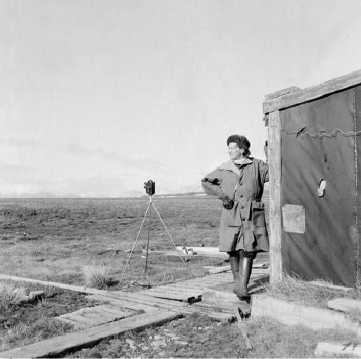 Herta Lampert med kamera rundt halsen og filmkamera på stativ ved fangstmann Arthur Oxaas sin fangsthytte på Kapp Wijk en gang på 1960-tallet. (Foto: Ukjent. Tromsø Museum – Universitetsmuseet.)