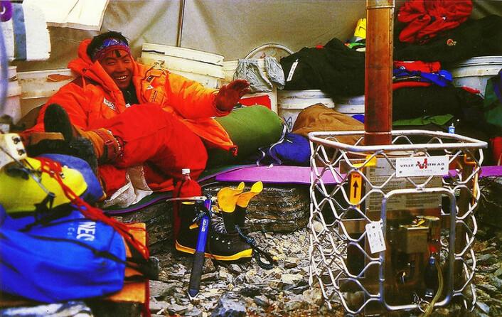 Forsvaret brukte tidligere vedovner til å varme opp telt. På 1980-tallet utviklet FFI en ovn drevet av diesel. Forsvaret testet den i flere år før de tok den i bruk for alvor i 1995-96, da de anskaffet 6000 nye teltovner basert på flytende brensel. Teltovnen M 94 ble i sin helhet utviklet og gjort produksjonsklar ved FFI. På en norsk ekspedisjon til Himalaya i 1996 kom ovnen til god nytte. Da fungerte den utmerket i en høyde på 6450 meter over havet. Sherpaen på bildet ser ut til å nyte varmen. Senere oppsto det uvær, og teltet ble besøkt av frosne klatrere fra andre ekspedisjonslag, som fikk igjen varmen der. (Foto: FFI)