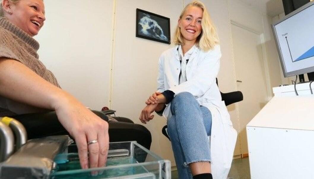 Slik ser det ut når du tar en smertetest med Andrea Milde Øhrn (til høyre). Smertetoleransen ble målt ved at deltakerne holdt handa i et kaldtvannsbad så lenge de kunne.  (Foto: Ronald Johansen)