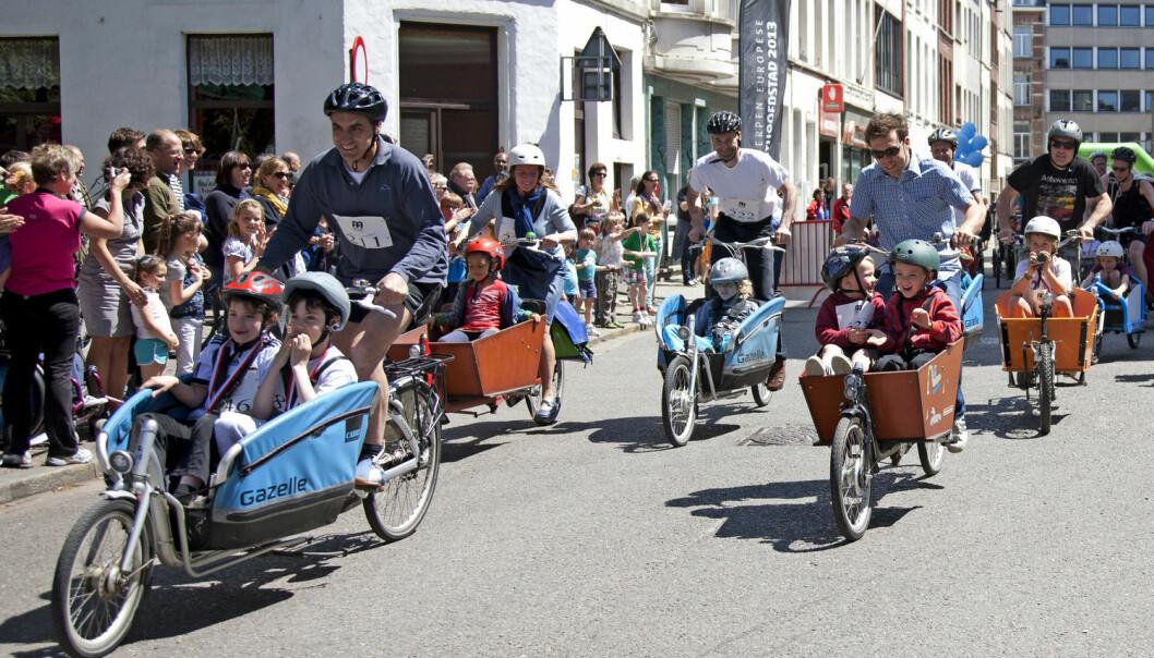 Foreldre og barn i et race for lastesykler i Belgia. Slike sykler har plass til posene og barna du normalt ikke får med deg på en vanlig sykkel. Lastesyklene gir deg mulighet til å øke aktivitetsnivået på en bærekraftig måte, skriver forskere fra Universitetet i Agder i denne kronikken.  (Illustrasjonsfoto: Virginia Mayo/AP Photo/NTB Scanpix)