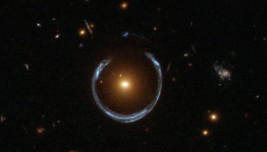 Dette er ikke en ring rundt en stjerne, selv om det ser sånn ut. Lyset fra en blålig galakse har blitt fordreid av en svært massiv, rød galakse i midten. Gravitasjonen gjør at lyset blir tøyd ut i tyngdefeltet. (Bilde: ESA/Hubble/NASA)