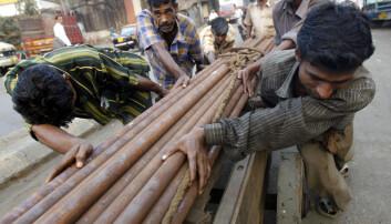 Indiske arbeidere trekker en vogn lastet med stålrør i Mumbai, India. (Foto: REUTERS/Arko Datta (INDIA)/NTB scanpix)