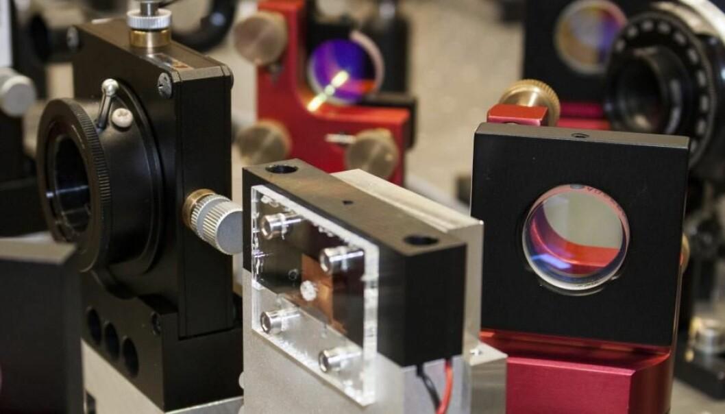 Ved DTU kan fysikerne eksperimentere med kvanteeffekter som senere kan brukes i en kvantedatamaskin. Magien oppstår i en krystall (i den svarte boksen i forgrunnen) som utsettes for laserlys. (Foto: Maria S. Bohn)