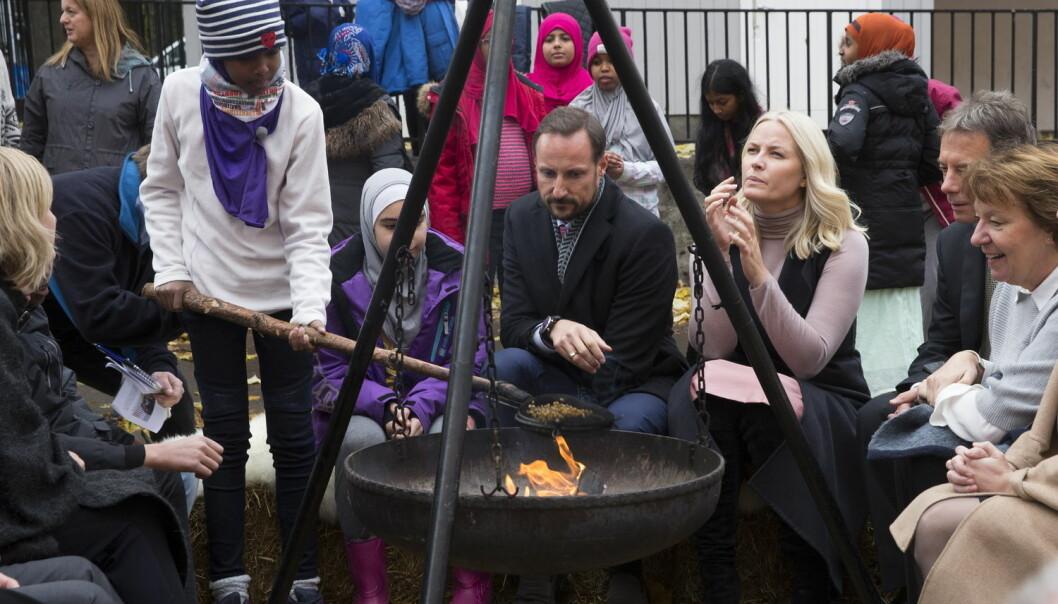 Kronprins Haakon og kronprinsesse Mette-Marit griller popkorn sammen med elever i skolegården under et besøk ved Tøyen skole i Oslo i november.  (Foto: Berit Roald / NTB scanpix)