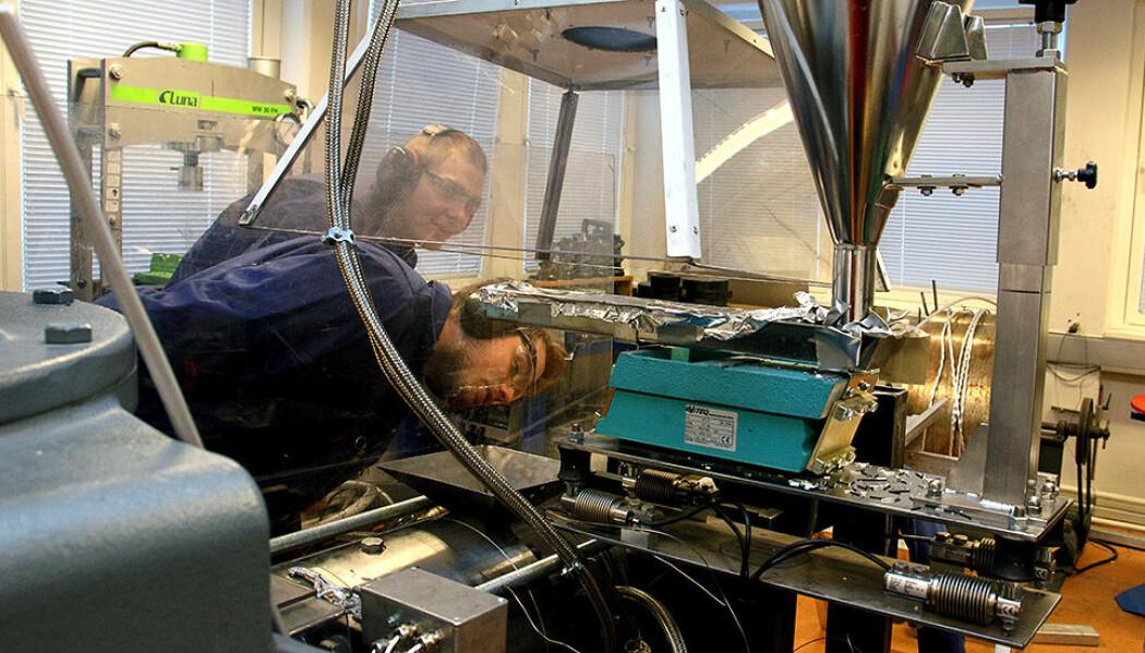 Stipendiat Geir Langelandsvik og masterstudent OlavRagnvaldsen overvåker en maskin som gjør biter av aluminium om til armering for betong. (Foto: Wenche Margrethe Kulmo/NTNU)