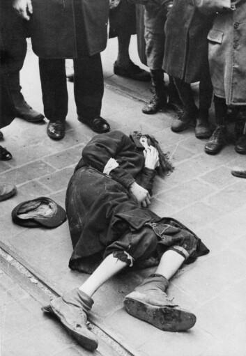 En mann har falt om i gaten, og en folkemengde samler seg rundt ham. Slike sterke scener ble daglig kost for de som ble tvunget til å leve i ghettoen i Warszawa mellom 1941 og 1943. Bildet er fra tidlig i 1941. (Foto: Albert Cusian og Erhard J. Knobloch / NTB scanpix)