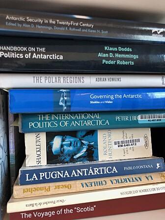 Stadig flere forskere og andre skriver om Antarktis. Her fra bokhylla på kontoret til Alejandra Mancilla, som foreløpig er nokså alene om å filosofere rundt Antarktis. (Foto: Bård Amundsen)