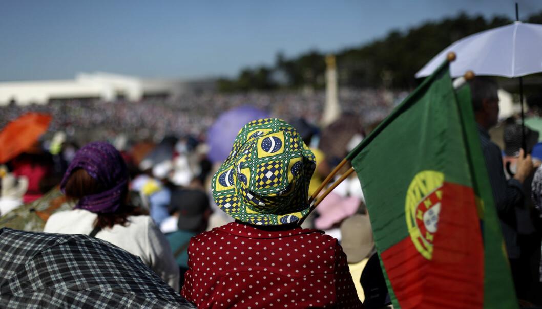 En kvinne med hatt med det brasilianske flagget på holder et portugisisk flagg under en pilgrimstur i Portugal. (Foto: AP Photo, Francisco Seco, NTB Scanpix)