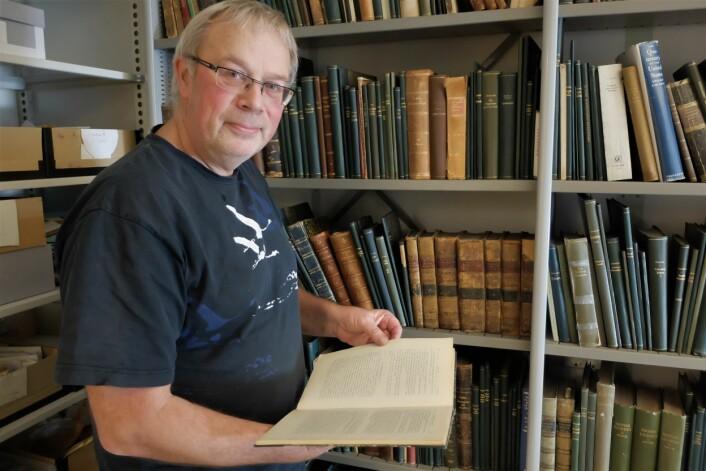 Førsteamanuensis Einar Timdal ved biblioteket til sin forgjenger Bernt Lynge. (Foto: Eivind Torgersen)