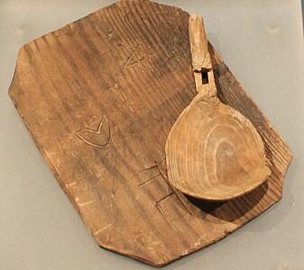 En skje og spisebrett fra reformasjonstiden. Disse ble funnet i Erkebispegården i Trondheim, og ble brukt av noen som jobbet på gården. De var sannsynligvis eid av samme person, siden de begge har innskåret det samme hjerteformede bumerket. (Foto: Chris McLees, Niku)