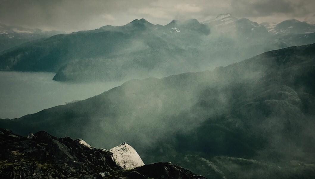 På kysten nord i Helgeland stiger bratte fjell rett opp av havet. Langs ryggen av Tonnesfjellet (foran) går grensen mellom de to jordskjelvkommunene Rødøy og Lurøy. (Foto: Bård Amundsen/forskning.no)