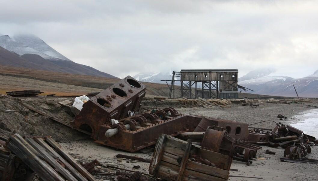 På dette bildet fra Hiorthamna ser vi i forgrunnen spor etter jernbaneskinner og et lokomotiv som har falt ned på stranden, og i bakgrunnen rester etter en taubanesentral. (Foto: NIKU/A.C. Flyen)