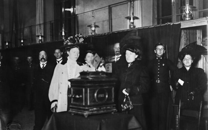 Første kvinne legger stemmeseddelen i urnen ved kommunevalget i Kristiania i 1910. På den tida kunne bare kvinner med en viss inntekt stemme. (Foto: ukjent/Oslo Museum, CC BY-SA 4.0)