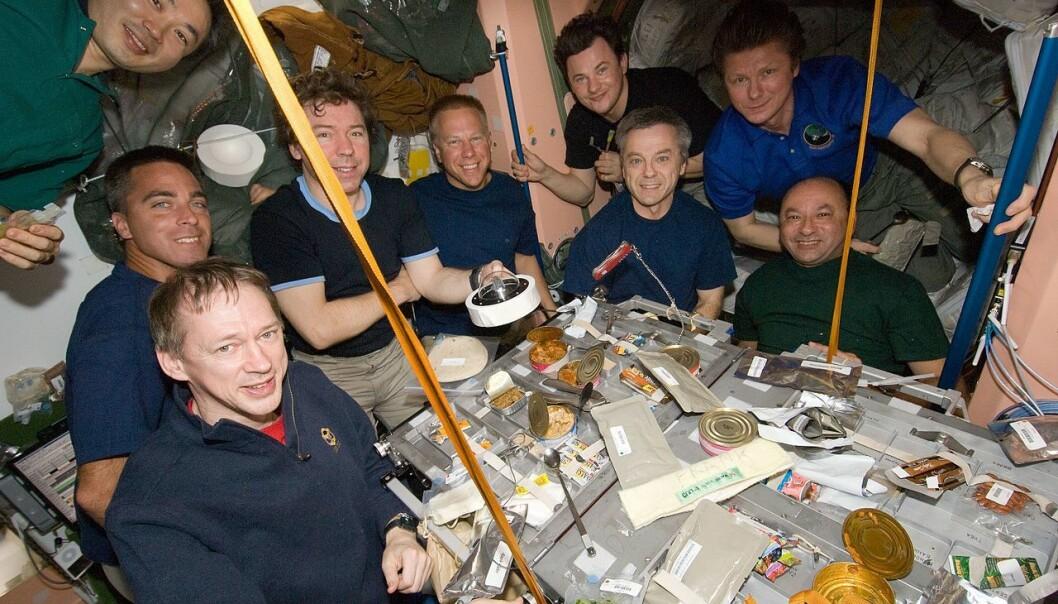 En hel gjeng med astronauter nyter et måltid på den Internasjonale romstasjonen i 2009. Mange, mange usynlige deltakere i form av bakterier og sopp er også med på festen. (Bilde: NASA)