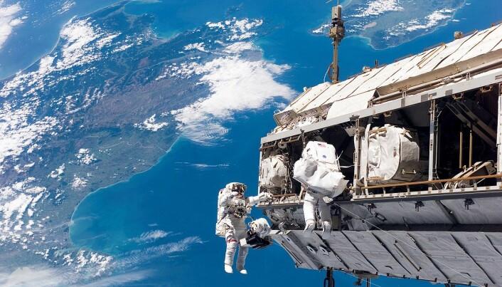Astronauter jobber på utsiden av romstasjonen - New Zealand kan sees i bakgrunnen. (Bilde:NASA)