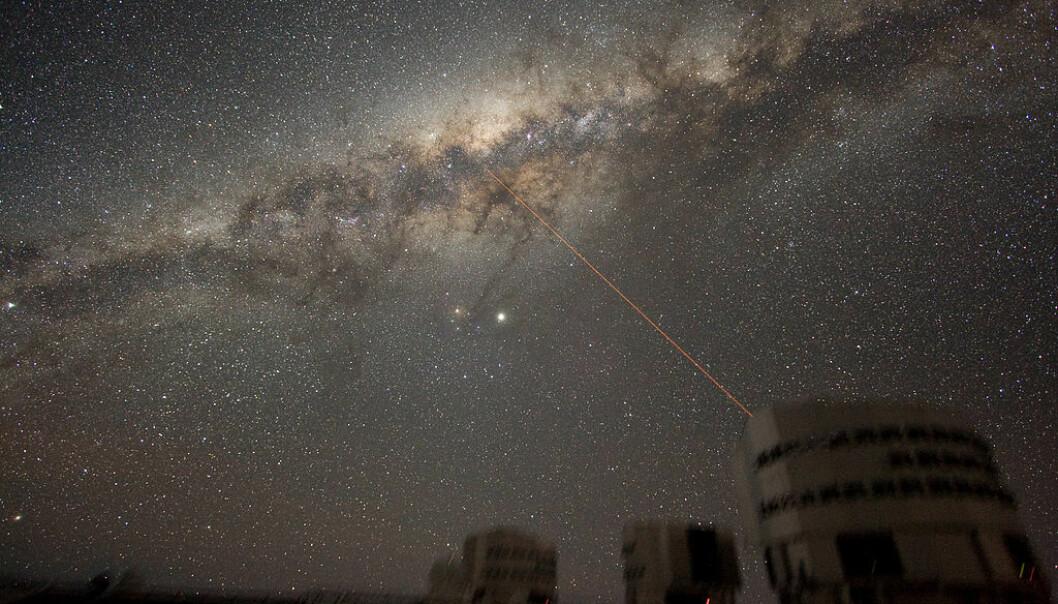 """Dette er Melkeveien i all sin prakt, slik vi ser den fra jorden. Er det noen der ute som prøver å få tak i oss? Dette er ESOs VLT-teleskop, og dette er bare et illustrasjonsbilde. Laserstrålen kommer fra teleskopet, bare så det er gjort klart. <p>(Illustrasjonsbilde: Y.Beletsky/ESO/<a href=""""https://creativecommons.org/licenses/by/3.0/"""">CC BY 3.0</a>)</p>"""