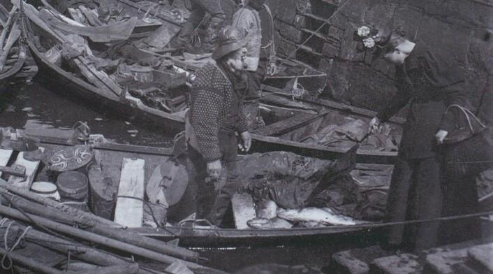 Ei kvinne frå Bergen kjøper fisk frå ved Bryggen. (Foto: (Opphav: K. Knudsen, Ukjent år. Billedsamlingen, UB Bergen.))