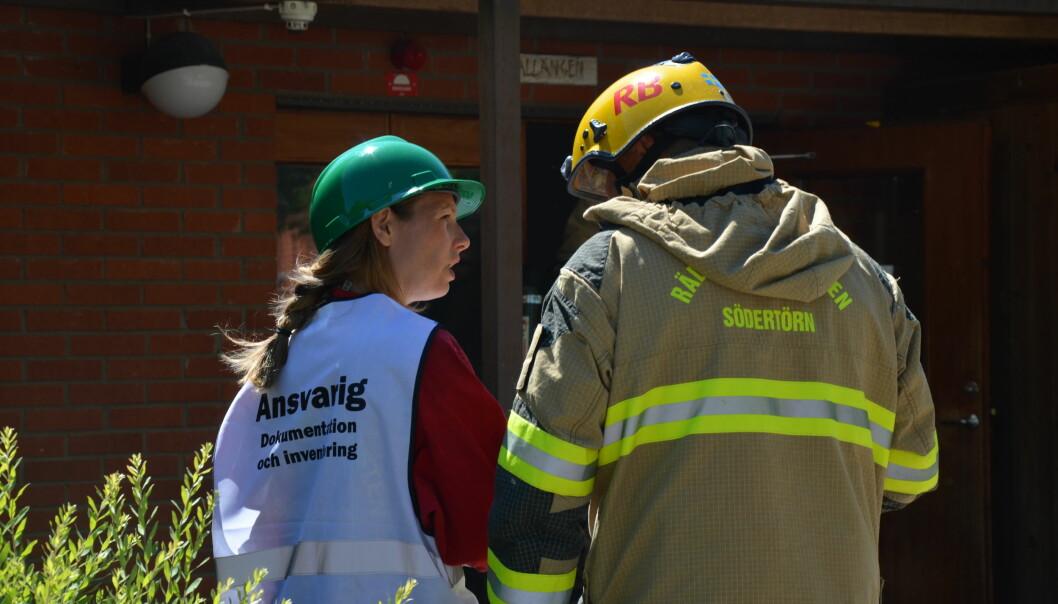 Nina Kjølsen Jernæs fra NIKU i samtale med brannvesenet under øvelse på redningsarbeid i kirke. Foto: Brannskyddsföreningen