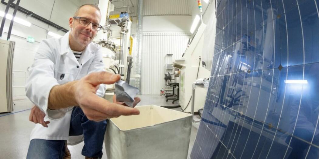 Sintef-forsker Martin Bellmann med det nye solcellepanelet. I hånda har han en bit av de nye materialet, som er laget av flis fra silisiumwafere. (Foto: Thor Nielsen)