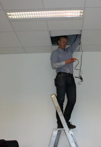 Ikke alt lar seg gjøre via fjernkontroll. Prosjektkoordinator Mads Mysen fra Sintef må stikke hodet opp i taket for å programmere spjeldene som kontrollerer ventilasjonen i klasserommet. (Foto: NILU)